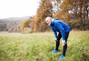Senior runner in blue jacket resting outside in sunny autumn nature.