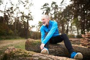 Senior runner in nature. Man sitting on wooden logs, resting, stretching, tying shoelaces.
