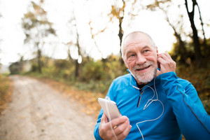 Senior runner in nature. Man with smart phone with earphones. Listening music or using a fitness app. Using phone app for tracking weight loss progress, running goal or summary of his run.