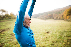 Senior runner in sunny autumn nature with earphones, listening music, doing stretching.