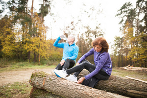 Senior runners in nature. Woman and man sitting on wooden logs, resting, drinking water.