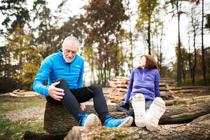 Senior runners in nature. Woman and man sitting on wooden logs.