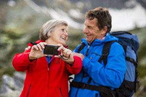 Senior tourist couple hiking and taking selfie at the beautiful mountains