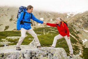Senior tourist couple hiking, man is helping woman to get to the rock