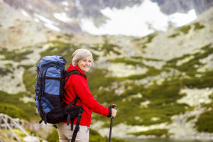 Senior tourist woman hiking at the beautiful mountains