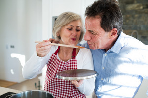 Senior woman and man in the kitchen cooking together, man tasting meal that woman is preparing.