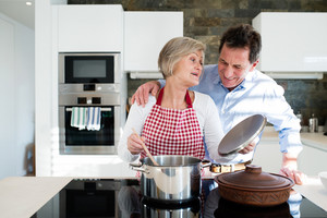 Senior woman and man in the kitchen cooking together.