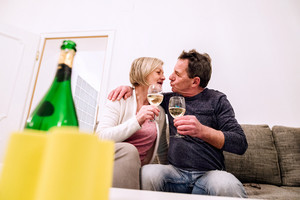 Senior woman and man sitting in living room on sofa, drinking champagne, kissing