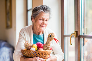 Senior woman at the window in her house holding basket with Easter eggs and straw hen