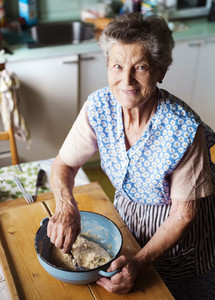 Senior woman baking pies in her home kitchen.  Kneading dough.