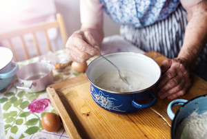 Senior woman baking pies in her home kitchen.  Making leaven.
