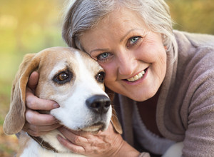 Senior woman hugs her beagle dog in countryside