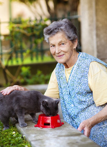 Senior woman in apron with her gray cat outside her house.