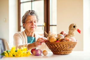 Senior woman in her house arranging basket with Easter eggs, straw hen and daffodils
