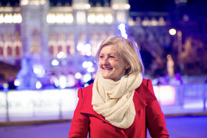 Senior woman in red winter coat and knitted scarf on a walk in illuminated night city. Historical building. Vienna, Austria.