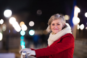 Senior woman in red winter coat and knitted scarf on a walk in illuminated night city. Vienna, Austria.