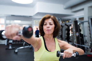 Senior woman in sports clothing in gym working out with weights. Close up of hands.