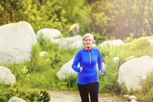 Senior woman jogging in beautiful nature, rocks in background