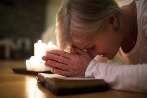 Senior woman kneeling on the floor praying with hands clasped together on her Bible. Burning candles next to her. Close up.