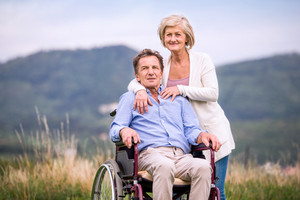 Senior woman pushing man sitting in wheelchair oustide in green autumn nature