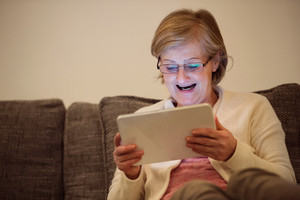 Senior woman with tablet sitting on couch in living room, reading something.