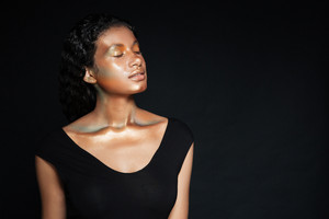 Sensual african american young woman with shining makeup standing with eyes closed over black background