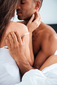 Sensual young couple hugging and making love in bed at home