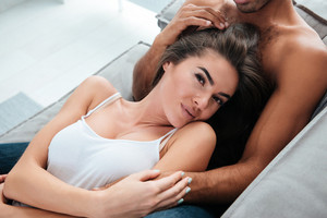 Sensual young couple lying and relaxing on sofa at home