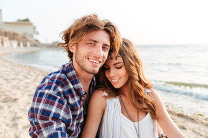 Sensual young couple sitting and smiling on the beach