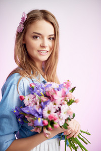 Serene woman with flowers looking at camera and smiling