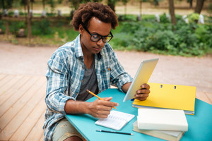Serious african young man writing and learning in the park