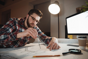 Serious bearded man in eyeglasses working over graph holding compass at the office