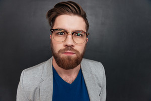 Serious bearded young businessman in glasses