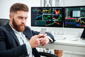 Serious bearded young businessman sitting and using mobile phone in office
