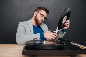 Serious bearded young man in glasses cutting vinyl record with scissors