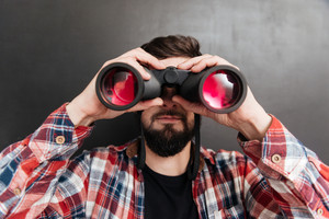 Serious bearded young man in plaid shirt standing and looking through binoculars over grey background