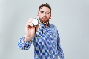 Serious bearded young man in plaid shirt using stethoscope over white background