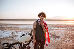 Serious brutal man wearing american flag cape and golden helmet standing near a motorcycle at the desert