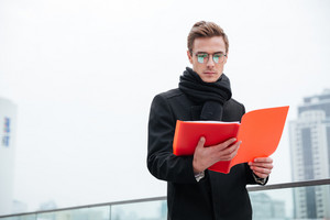Serious Business man in glasses and warm clothes reading documents outdoors
