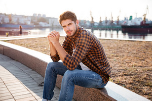 Serious confident young man in plaid shirt sitting outdoors