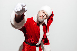 Serious frowning man santa claus standing and pointing on you