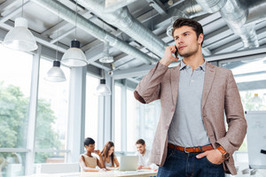 Serious handsome young businessman standing and talking on mobile phone in office