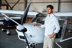 Serious handsome young man standing near small airplane