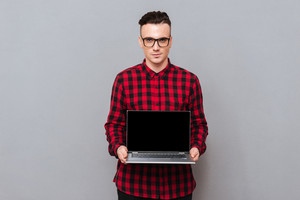 Serious Hipster showing blank laptop screen and looking at camera. Isolated gray background