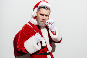 Serious man santa claus with present sack standing and smoking