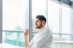 Serious pensive young businessman sitting and thinking in office
