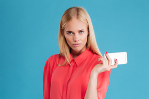 Serious pretty blonde girl holding mobile phone and looking at camera over blue background