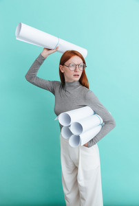 Serious redhead young woman holding and throwing blueprints over blue background