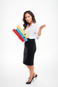 Serious smart asian businesswoman holding colorful binders waving hand over white background