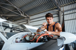 Serious young aircraft mechanic standing and fixing small airplane